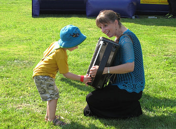 Donna Rhodenizer with accordion and young child